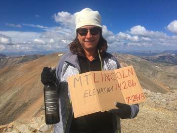 Kim Brown atop Mt Lincoln with bottle of Quandary wine